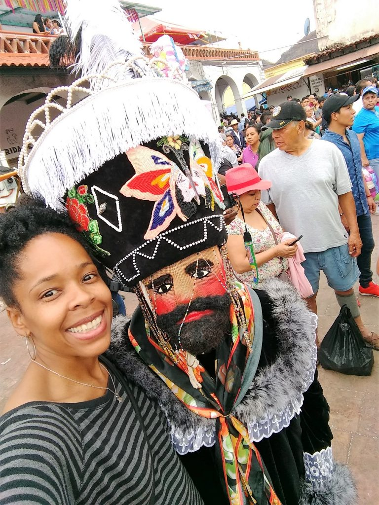 me and a person dressed as a Chinelo during carnival