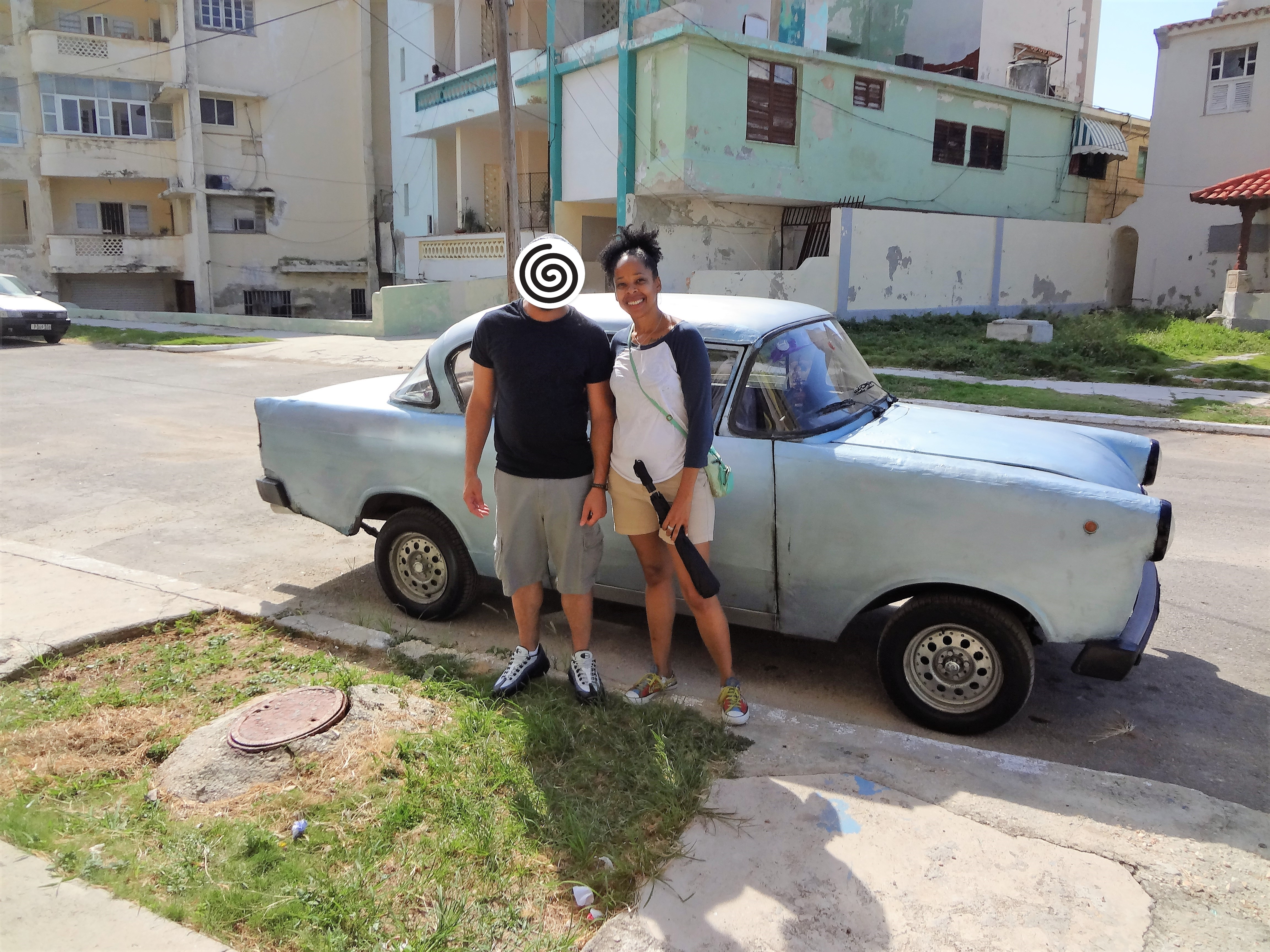 Couple in front of car on street in Cuba