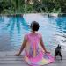 woman and dog sitting near pool