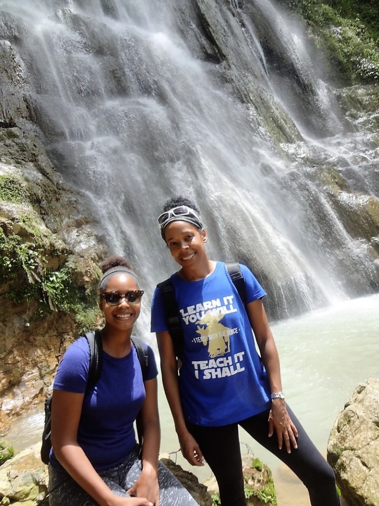 Two women standing in frontof a waterfall
