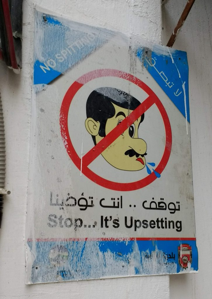 no spitting sign in English and Arabic