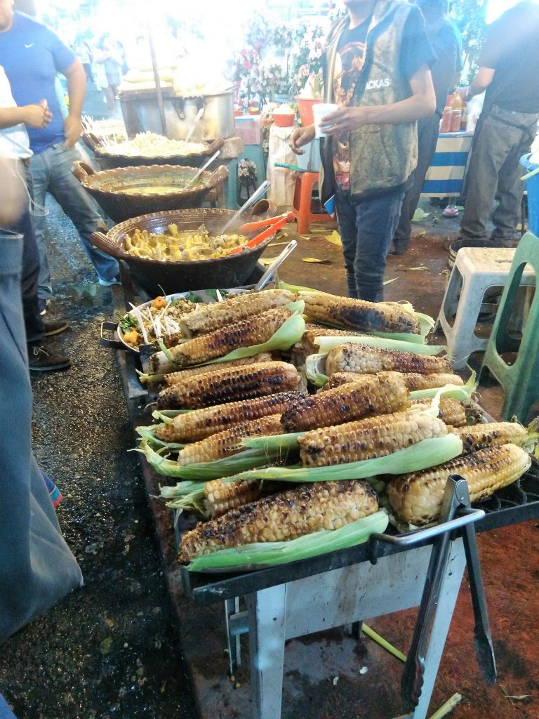 Street food vendor selling roasted corn, elote and esquites