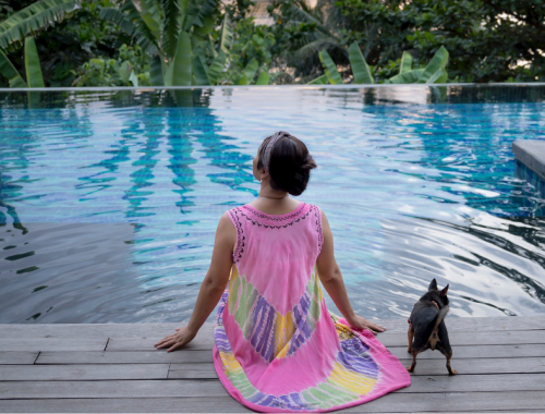 woman and dog sitting near pool