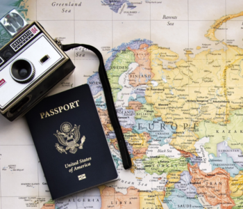 camera and passport on top of world map